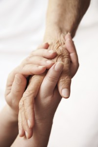 Elderly hands held in younger hands